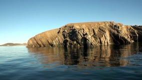 Каменные утесы среди поверхности воды Северного океана на новой земле акции видеоматериалы
