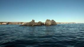 Каменные утесы среди поверхности воды Северного океана на новой земле видеоматериал