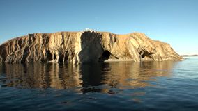 Каменные утесы среди поверхности воды Северного океана на новой земле сток-видео