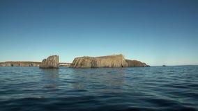 Каменные утесы среди водообильной поверхности Северного океана на новой земле акции видеоматериалы