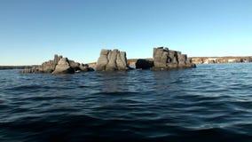 Каменные утесы среди водообильной поверхности Северного океана на новой земле сток-видео