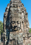 Каменный Будда смотрит на Angkor Wat в Камбодже Стоковое фото RF