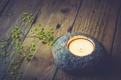 Каменный держатель для свечи с светом чая на постаретой деревянной предпосылке, чувствительных желтых цветках Стоковая Фотография RF