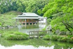 Каменный мост с отражением и здание павильона в Дзэн садовничают Стоковые Изображения