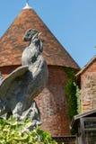 Каменный петушок против дома Oast Кента стоковое изображение rf
