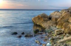 Каменный пляж на заходе солнца Стоковые Фотографии RF
