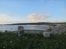 Каменный стенд на пляже обозревает залива на море Стоковая Фотография