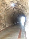 Каменный тоннель с светом в ем другая сторона ` s Стоковая Фотография RF