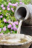 Каменный фонтан с цветками на предпосылке Стоковые Изображения