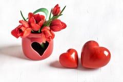 2 каменных сердца и пука красных тюльпанов на белизне Стоковая Фотография RF