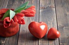 2 каменных сердца и пука красных тюльпанов на деревянной предпосылке Стоковое Изображение