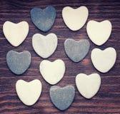 12 каменных сердец помещенных славно на винтажной древесине Стоковое фото RF