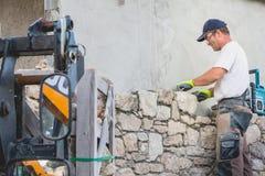 Каменщик восстанавливает дом с камнем в традиции NOIRMOUTI Стоковые Фото