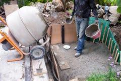 Каменщик делая малый пруд в саде стоковые изображения rf