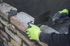 Каменщик кирпича используя лопатку для того чтобы распространить миномет 2 Стоковые Изображения
