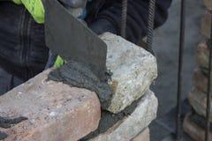 Каменщик кирпича используя лопатку для того чтобы распространить миномет Стоковая Фотография RF