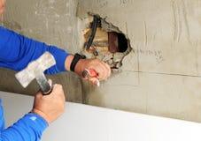 Каменщик подготавливая отверстие в стене для того чтобы установить выходы коробки электрические для реновации дома стоковое фото