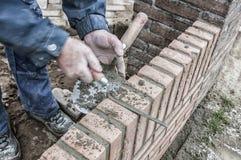 Каменщик работая с кирпичами стоковая фотография