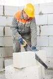 Каменщик работника каменщика с ручной пилой стоковое фото