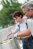 Каменщик с тренирующей молодой женщины на работе Стоковая Фотография RF