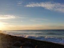 Камень воды солнца облака пляжа моря вниз стоковые изображения