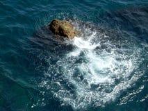Камень в воде окруженной пеной Стоковое Изображение