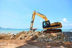 Камень землекопа экскаватора работая на строительной площадке - затяжелителе backhoe на предпосылке океана моря пляжа и голубого  стоковые фотографии rf