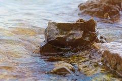 Камень около реки Волны, который побежали на береговой линии Заход солнца лета Лучи солнца отражены в воде стоковые изображения rf