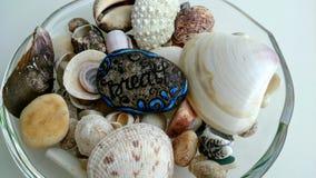 Камень с надписью дышает лож в чашке среди seashells стоковые фото
