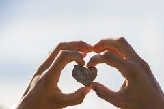 Камень с формой сердца в руке женщины Стоковые Изображения RF