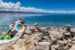 Камень Marnyi с лентами sutra на береге озера Namtso Стоковые Фотографии RF