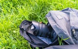 Камера вставляет из рюкзака лежа на конце-вверх травы стоковое изображение