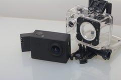 Камера действия лежит на белой поверхности Около коробки для подводной стрельбы и запасной батареи Стоковые Фото