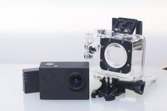 Камера действия лежит на белой поверхности Около коробки для подводной стрельбы и запасной батареи Стоковые Фотографии RF