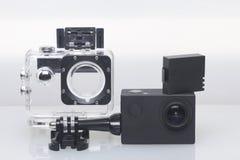 Камера действия лежит на белой поверхности Около коробки для подводной стрельбы и запасной батареи Стоковая Фотография