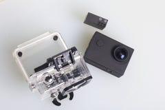 Камера действия лежит на белой поверхности Около коробки для подводной стрельбы и запасной батареи над взглядом Стоковые Фото