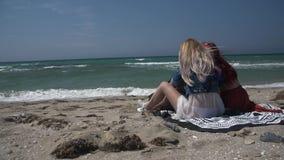 Камера замедленного движения объезжает 2 молодых сексуальных женщин ослабляя на песчаном пляже с собакой сток-видео