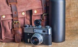 Камера и портфель на таблице стоковое изображение