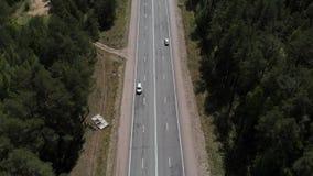 Камера летает над дорогой в древесинах, камера снимает вниз r акции видеоматериалы