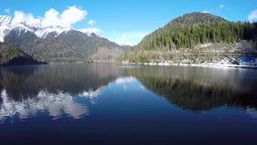 Камера медленно поднимает над покрытым снег озером горы видеоматериал