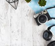 Камера, наушники, заводы, и оформление на белом столе Стоковые Изображения