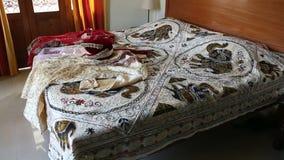 Камера показывает большую кровать и индийские платья свадьбы на ей