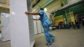 Камера показывает работника в голубом равномерном нажимая холодильнике акции видеоматериалы