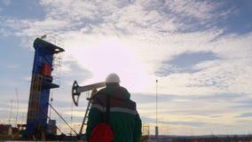 Камера показывает работника идя против нефтяной скважины и деррик-крана акции видеоматериалы