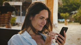 Камера сигналит внутри на счастливой молодой кавказской женщине используя отдыхать приложения покупок смартфона усмехаясь на экзо видеоматериал
