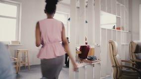 Камера следовать Афро-американской женщиной босс входит офис, дает направления к работникам Многонациональная сыгранность 4K груп акции видеоматериалы
