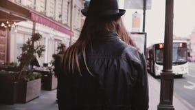 Камера следовать девушкой детенышей местной в кожаной куртке и стильной шляпе идя вдоль замедленного движения улицы города, шины  видеоматериал