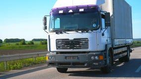 Камера следовать для того чтобы перевезти на грузовиках с трейлером груза управляя на шоссе и транспортируя товары на летний день видеоматериал