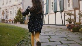 Камера следовать маленькой девочкой бежать на вымощенной дороге задний взгляд Старые полу-timbered дома в Hattingen, Германии 4K видеоматериал