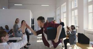Камера следовать счастливым молодым кавказским бизнесменом празднуя достижение вместе с многонациональными работниками офиса акции видеоматериалы